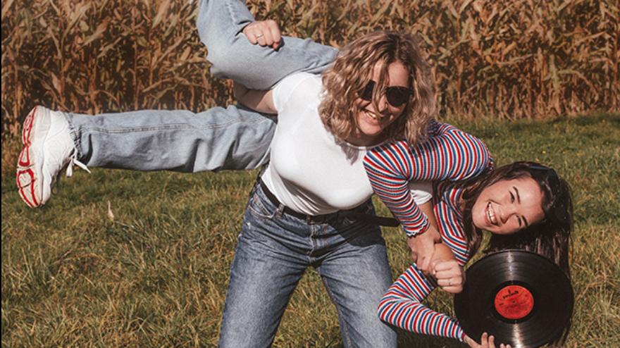 zdjęcie dwóch dziewczyn na tle pola z kukurydzą, jedna trzyma drugą na plecach, uśmiechnięte twarze, w ręku płyta winylowa